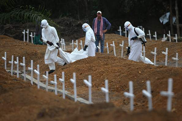 Men in white hazmat suits in a graveyard.